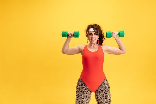 黄色の壁で若い女性モデルのトレーニング