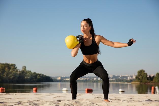 晴れた日に屋外でトレーニングする若い女性モデル