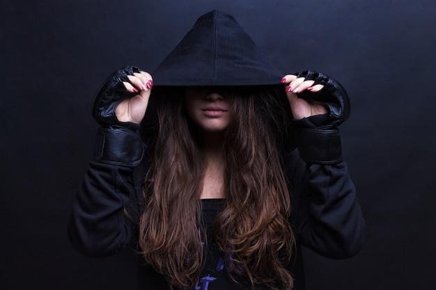 スポーツフード付きスウェットシャツ黒の背景を身に着けている若い女性モデル