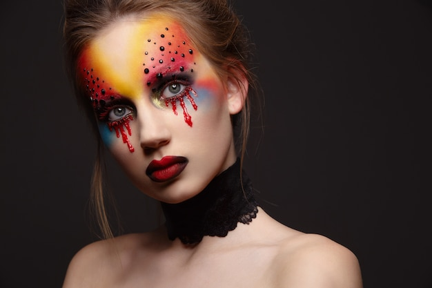 Young female model with bloody eyes makeup
