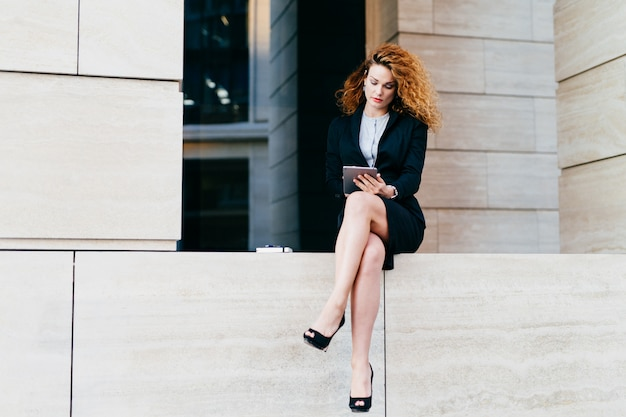 Young female model with curly hair, wearing elegant suit and high-heeled shoes, having slender legs, using modern tablet for communication