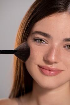 메이크업 브러시로 젊은 여성 모델