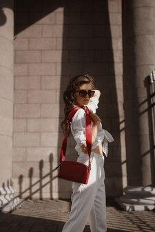 流行のサングラスをかけた完璧なスリムなボディと白いズボンとシャツを着た若い女性モデルが、ヨーロッパの街の歩道を歩く