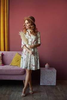 ベージュの帽子と夏のドレスのスリムな体型の若い女性モデルは、脇を見てピンクのインテリアでポーズをとる