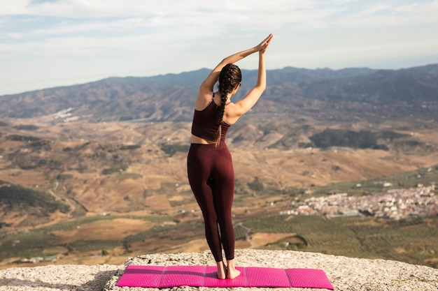 Young female on mountain practicing yoga