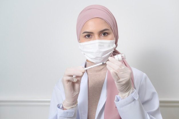 A young female muslim doctor holding a syringe with covid-19 vaccine bottle for injection, covid-19 vaccination and health care concept