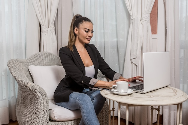 Young female networking in hotel room