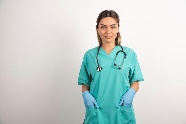 Молодая медсестра позирует, одетый в медицинский халат.