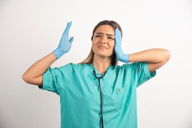 聴診器でポーズをとる若い女性看護師。