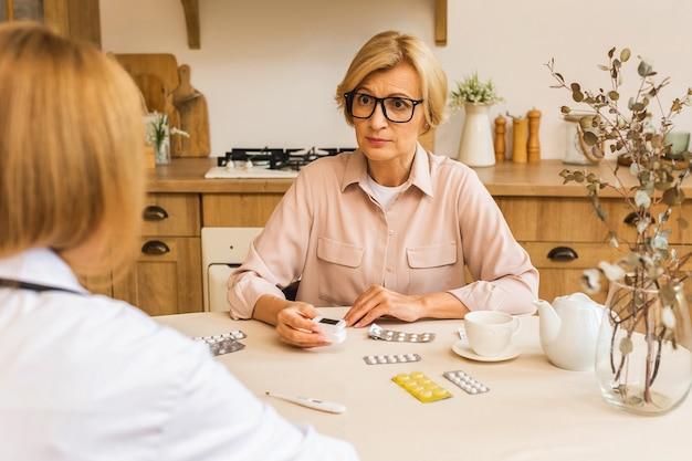 Молодая медсестра обеспечивает уход, медицинское обслуживание помогает поддерживать пожилую зрелую женщину на домашнем медицинском посещении, женщина-медсестра проявляет сочувствие, поощряет пенсионера на кухне.