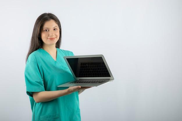 白の上に立っているラップトップを持つ若い女性の看護師。
