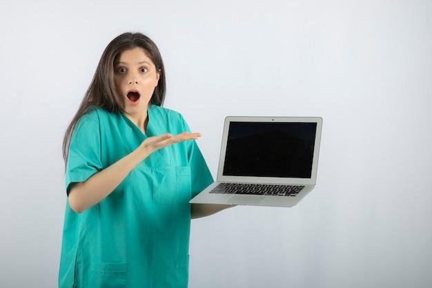La giovane infermiera femminile con il computer portatile ha sorpreso circa qualcosa su bianco.
