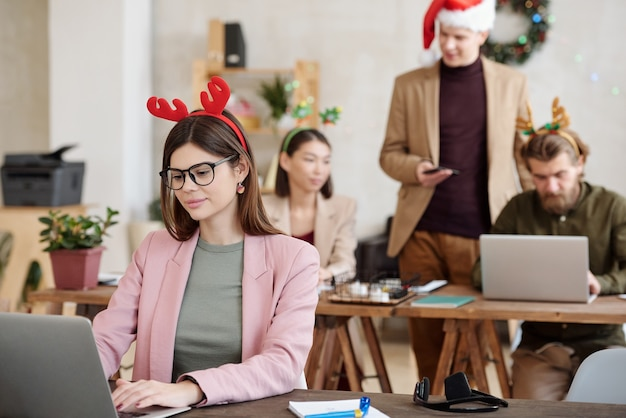 Young female office manager in eyeglasses, smart casualwear and christmas headwear networking in front of laptop against colleagues