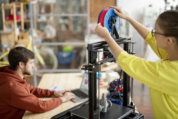Young female office worker changing spool with red filament on 3d printer with colleague networking