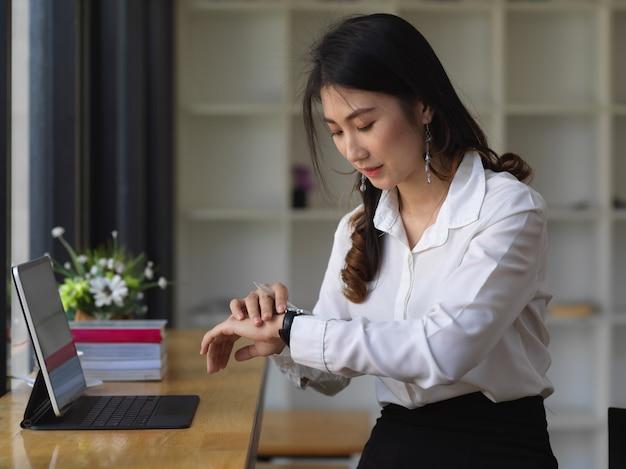 Молодой женский офисный работник, проверяющий время с ее часами в офисной комнате
