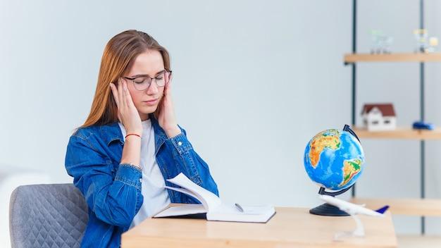 若い女性会社員は、一生懸命働いた後頭痛を持っています。疲労と働き過ぎの少女が寺院に手を伸ばしている。