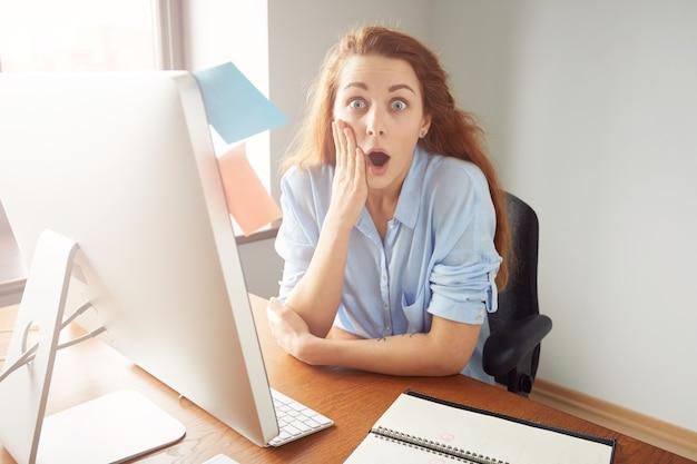 Молодая женщина-офисный работник выглядит удивленным и шокированным