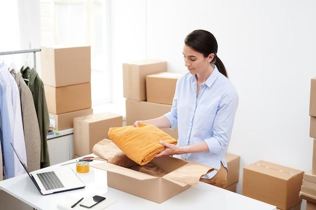 Менеджер интернет-магазина молодой женщины кладет сложенные бархатные желтые брюки в коробку во время упаковки заказа клиента