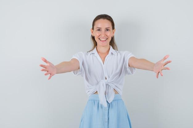 Giovane donna che apre le braccia per abbraccio in camicetta e gonna e sembra allegra