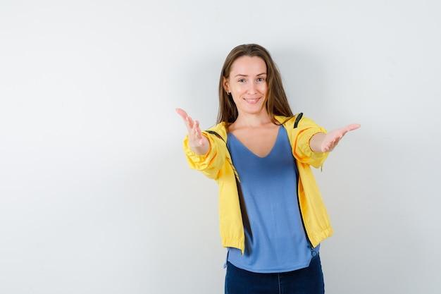 Braccia di apertura femminile giovane per abbraccio in t-shirt, giacca e guardando allegro. vista frontale.