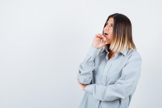 Giovane donna in camicia oversize che tiene la mano sotto il mento e sembra perplessa, vista frontale.