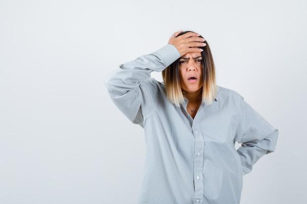 Giovane donna in camicia oversize che tiene la mano sulla fronte mentre tiene la mano sull'anca e sembra smemorata, vista frontale.