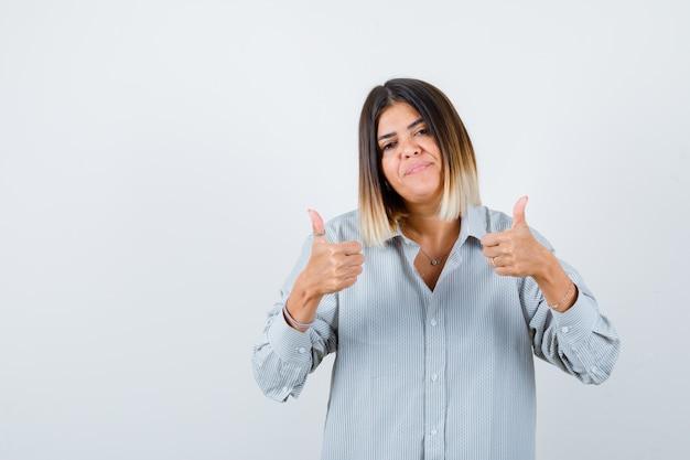 Giovane donna in camicia oversize che mostra i pollici in su e sembra felice, vista frontale.