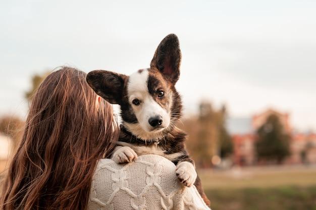 秋の公園で赤い毛布の格子縞にウェールズのコーギー犬を抱いて若い女性所有者の女性