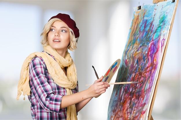 Молодая художница, держащая палитру и кисти на светлом фоне