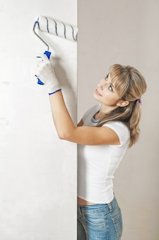Young female painting the wall