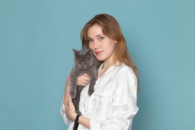 Giovane femmina in pigiama e che tiene piccolo gattino grigio carino sul blu