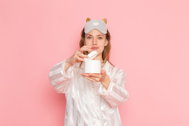 Young female in pajamas and sleep mask holding can of cream on pink