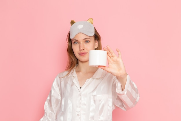 Young female in pajamas and sleep mask holding cream with smile on pink