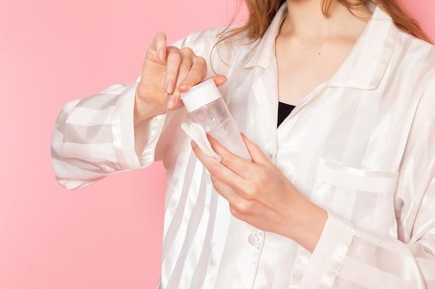 Giovane donna in pigiama e maschera per dormire tenendo spray per il trucco sul rosa