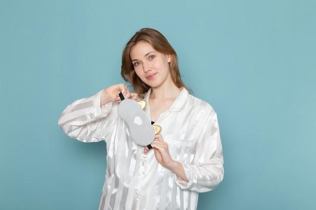 Giovane donna in pigiama e maschera per dormire sorridente e posa sul blu