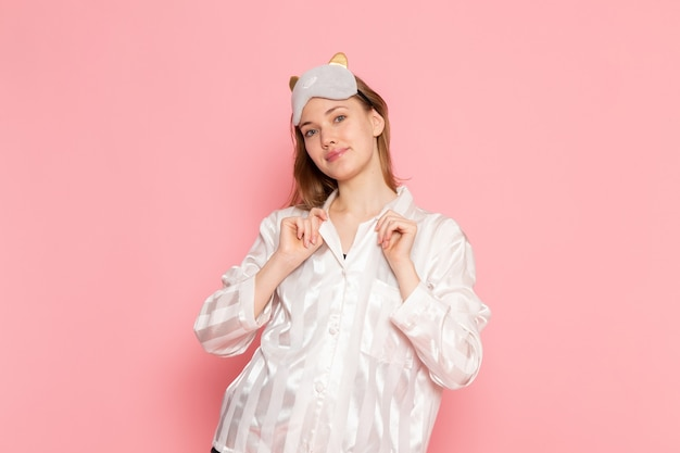 Young female in pajamas and sleep mask standing and posing with smile on pink