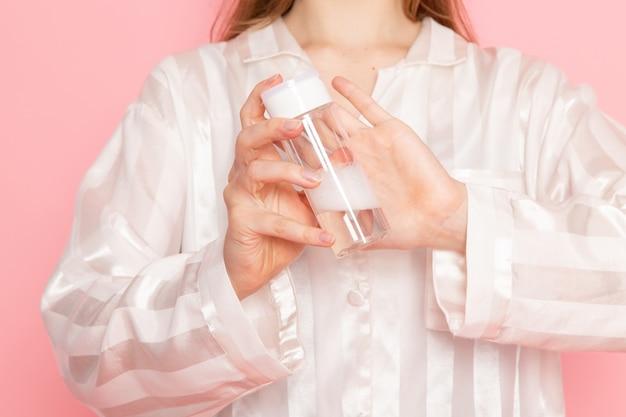 Giovane donna in pigiama e maschera per dormire utilizzando spray per il trucco sul rosa