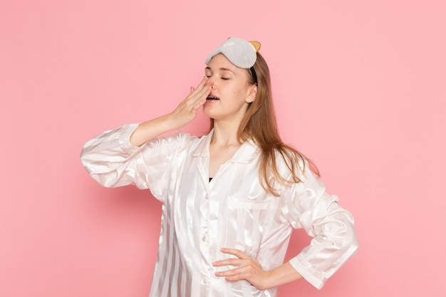 Young female in pajamas and sleep mask yawning badly on pink