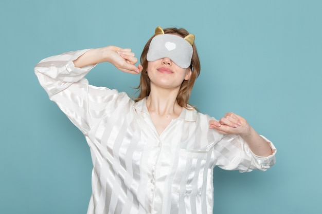 Young female in pajamas and sleep mask yawning with it on blue