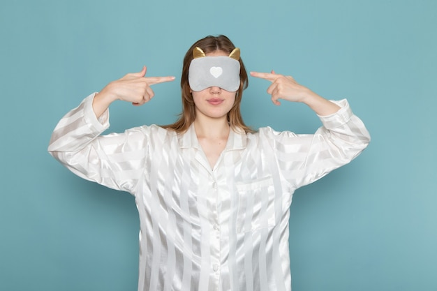 Young female in pajamas wearing sleep mask on blue