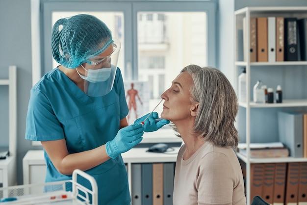 Молодая женщина-фельдшер использует мазок из носа, чтобы сделать тест на коронавирус зрелой женщине во время работы в больнице