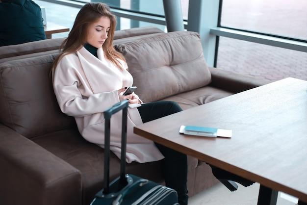 공항에서 전화를 사용하는 젊은 여성 승객.