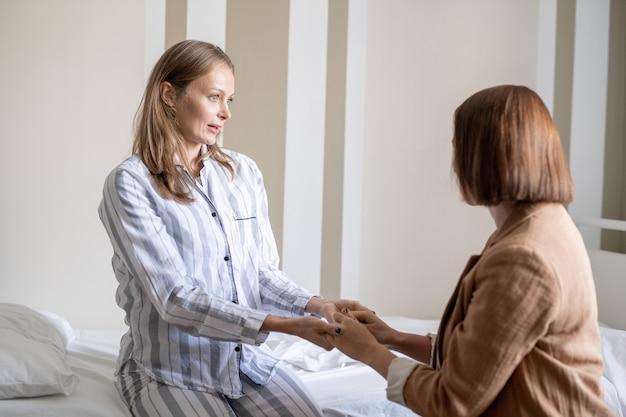 코비드 병원의 젊은 여성 환자는 치료, 처방 및 회복에 대해 대화하는 동안 친구 앞에서 침대에 앉아 있습니다.
