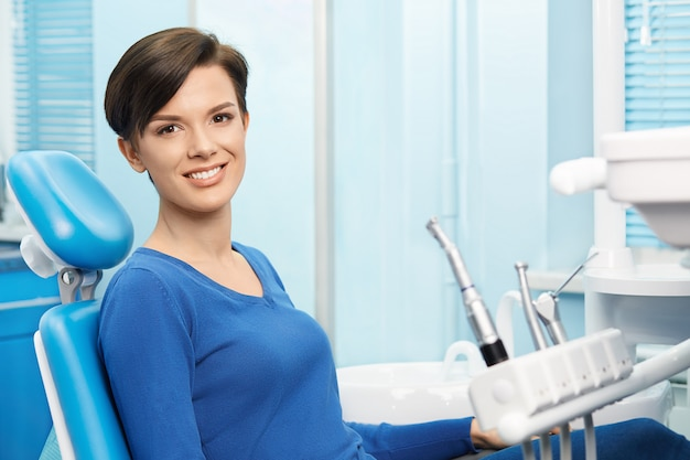 Young female patient visiting dentist office. beautiful smiling woman with healthy straight white teeth sitting at dental chair. dental clinic. stomatology