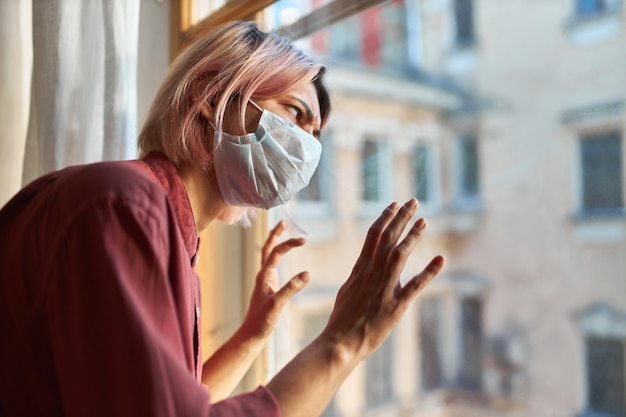 Covid-19 증상을 가진 젊은 여성 환자는 격리 기간 동안 병원에 머물러야하며, 일회용 수술 용 마스크의 창가에 서서 편집증적인 표정을 강조하고 유리에 손을 대고 있어야합니다.