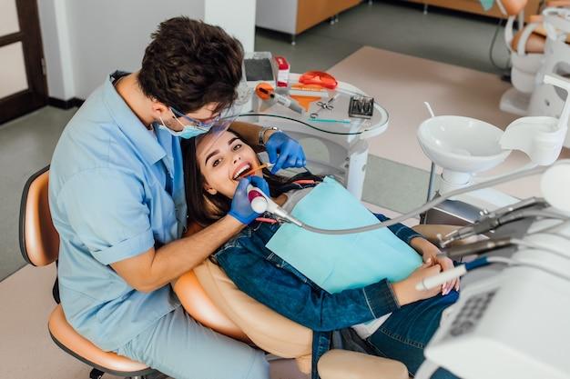 치과 의사 사무실에서 치과 검사를 검사하는 입을 벌리고 있는 젊은 여성 환자.