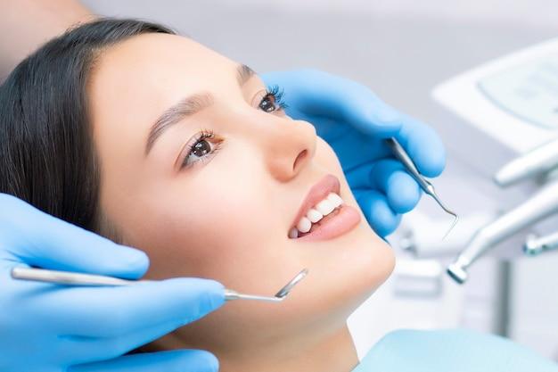 Молодая пациентка с красивой улыбкой изучает стоматологический осмотр