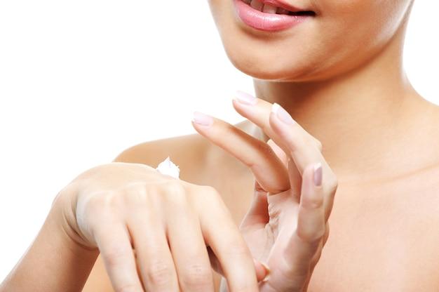 화장품 크림을 적용하는 그녀의 손을 돌보는 젊은 여성 사람