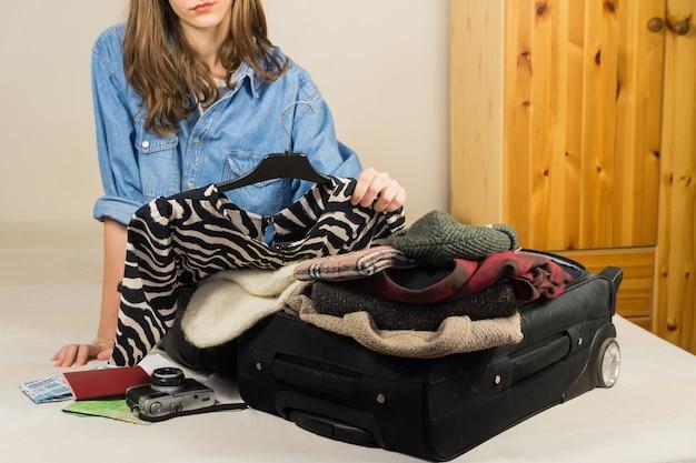 北の寒い国で休暇を取るためにドレスとアクセサリーを選ぶ若い女性