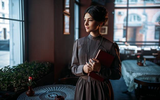本と窓の近くに立っている若い女性の人
